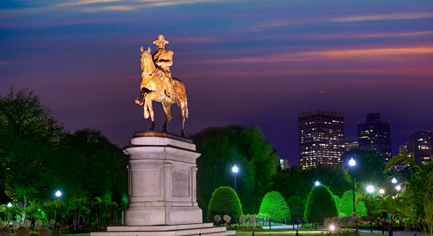 Bronze statue of George Washington lit up at dusk against a backdrop of lush greenery and blue and purple skies