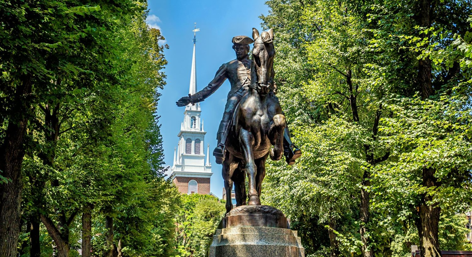 Bronze statue of Paul Revere amidst a backdrop of lush greenery, blue skies, and top of a white church steeple