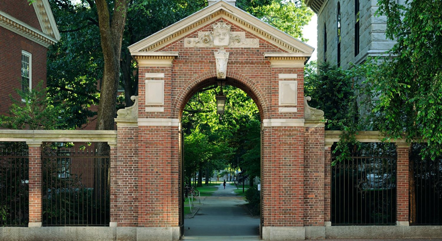 Red and beige brick arched gated entry to a lush green campus