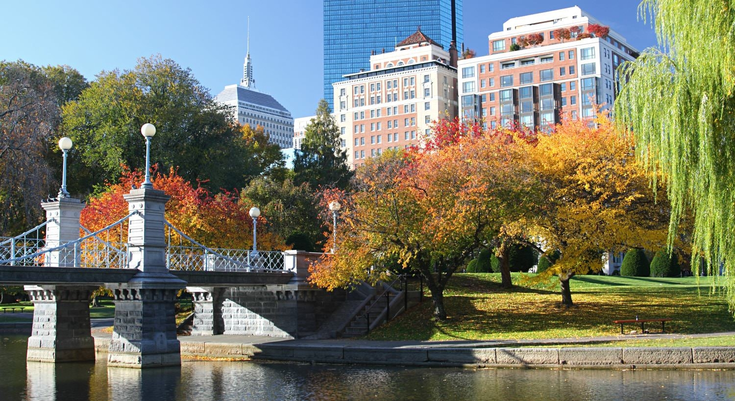 Gray and white stone bridge near a park of autumn hued trees and city buildings in the background