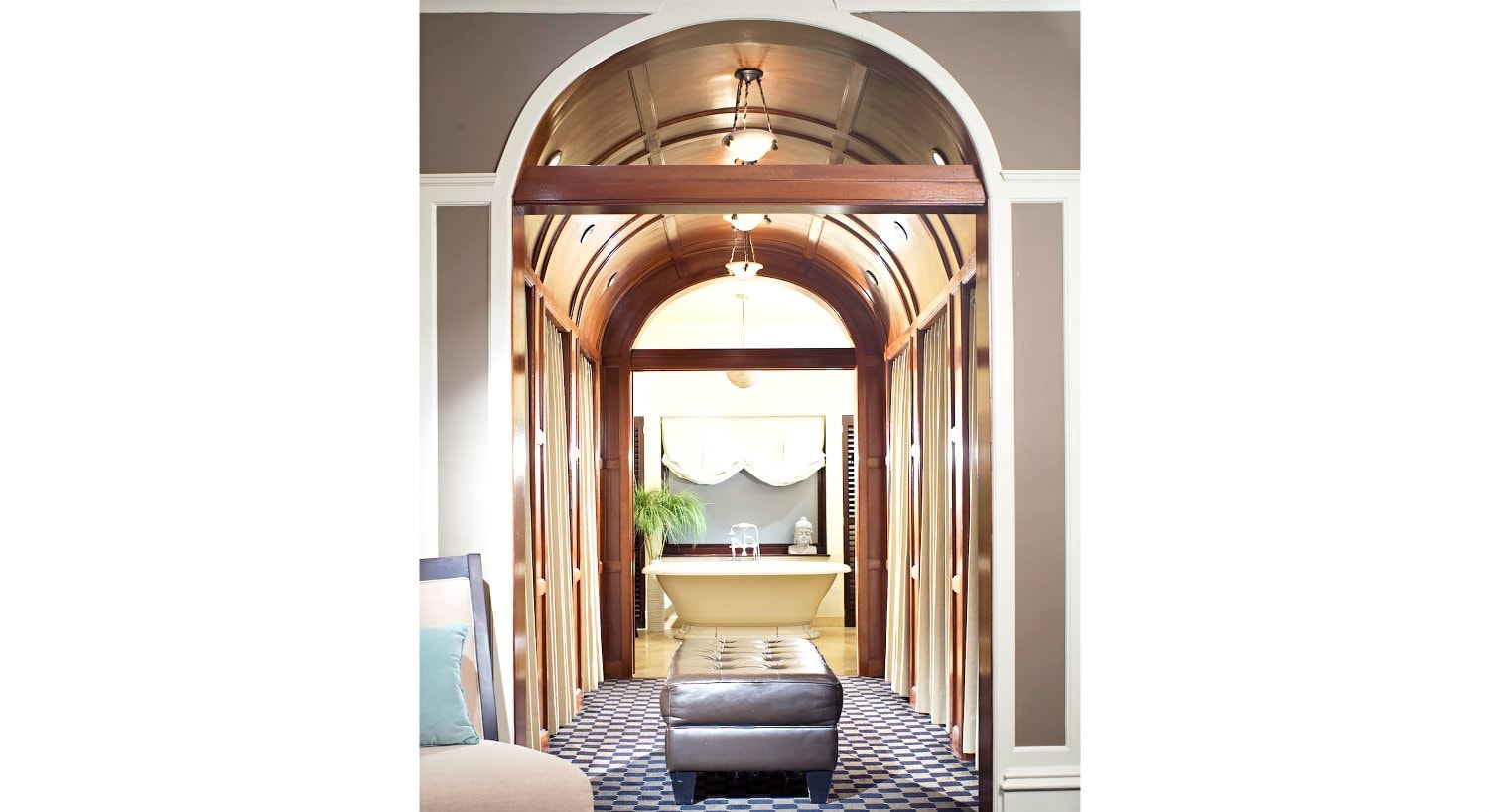 View of white modern freestanding tub through a stained wood hallway with barrel vault ceiling