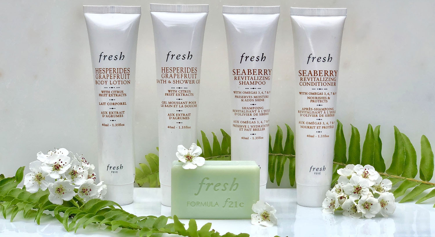 Four white bottles of Fresh brand bathroom amenities, with green bar of soap, green fern fronds and white pear blossoms.