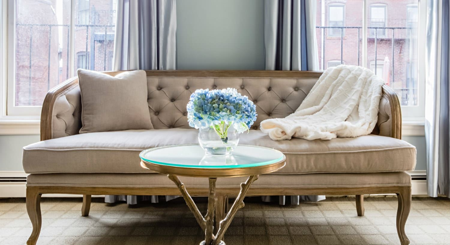 Beige settee in front of two windows with silver curtains and a small round coffee table with blue flowers