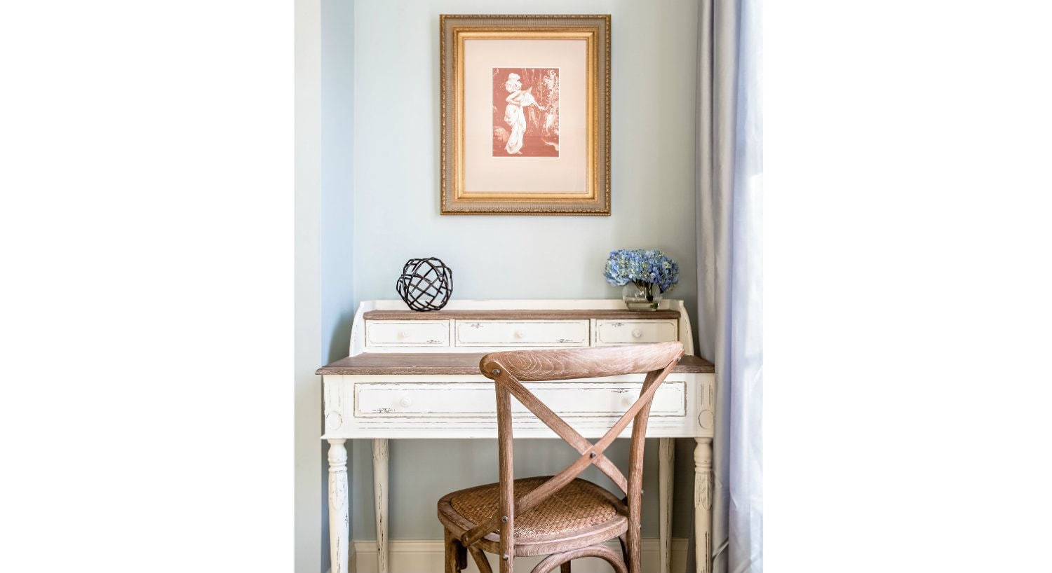 White painted secretary desk with wood and wicker chair tucked into a niche