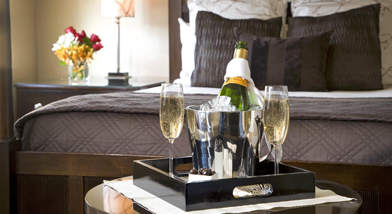lack tray of champagne chilling in silver bucket and two filled champagne flutes with view of elegant bed in background