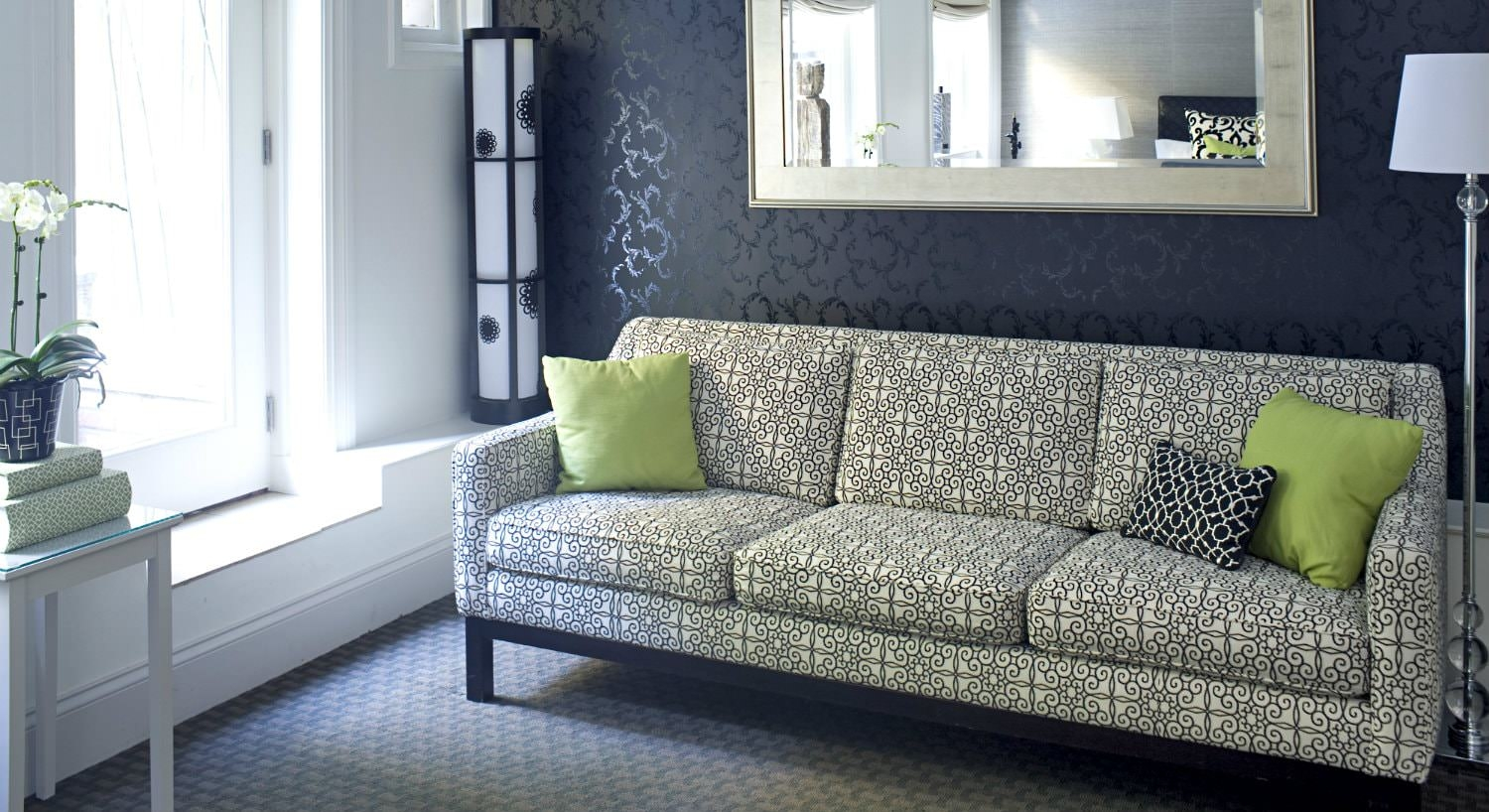 Black and white sofa with lime green pillows in front of an elegant black papered wall with hanging mirror