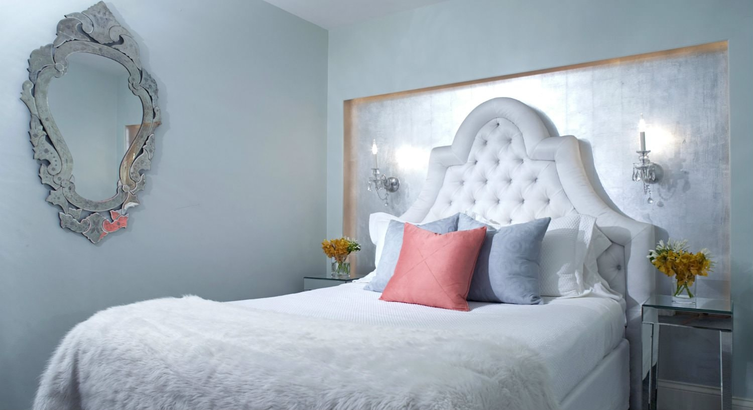 guest room with ornate silver mirror, decorative white upholstered headboard, and white fur blanket