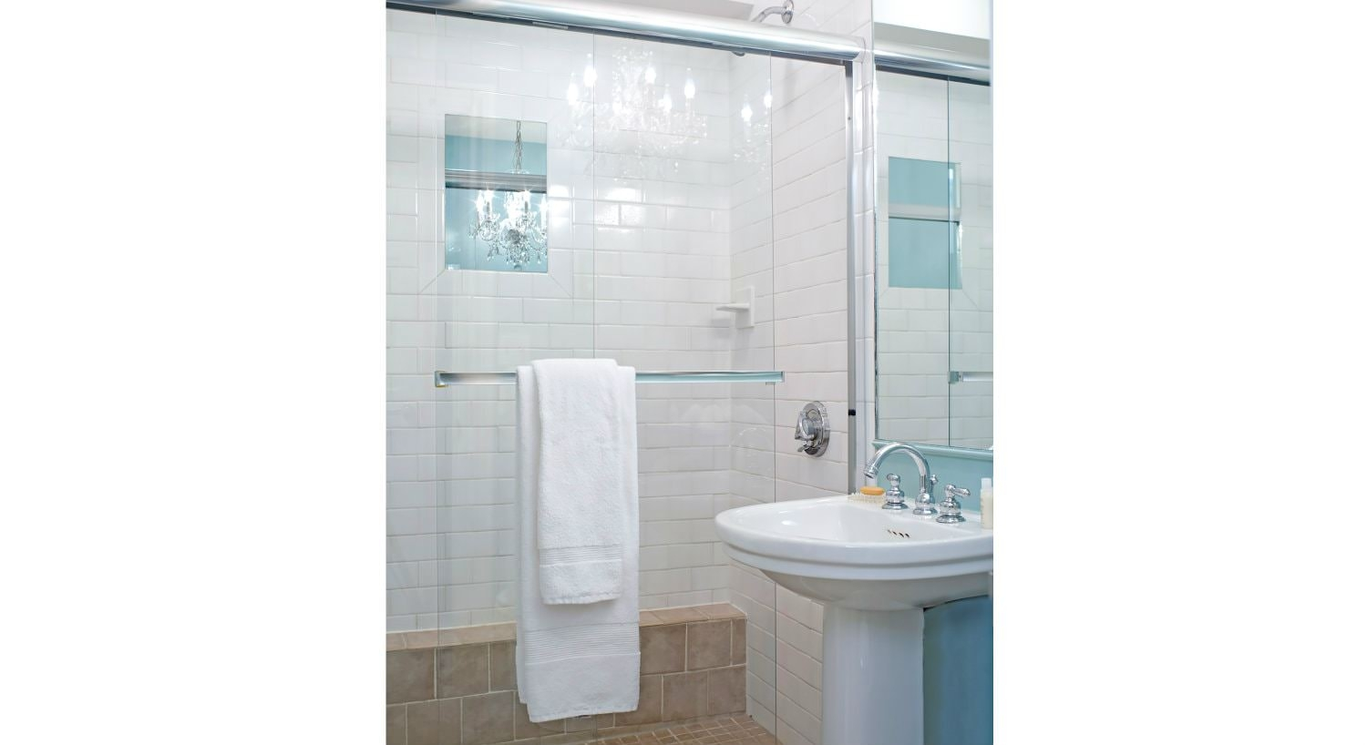 White and blue bathroom with tiled walk-in shower with glass doors and white pedestal sink