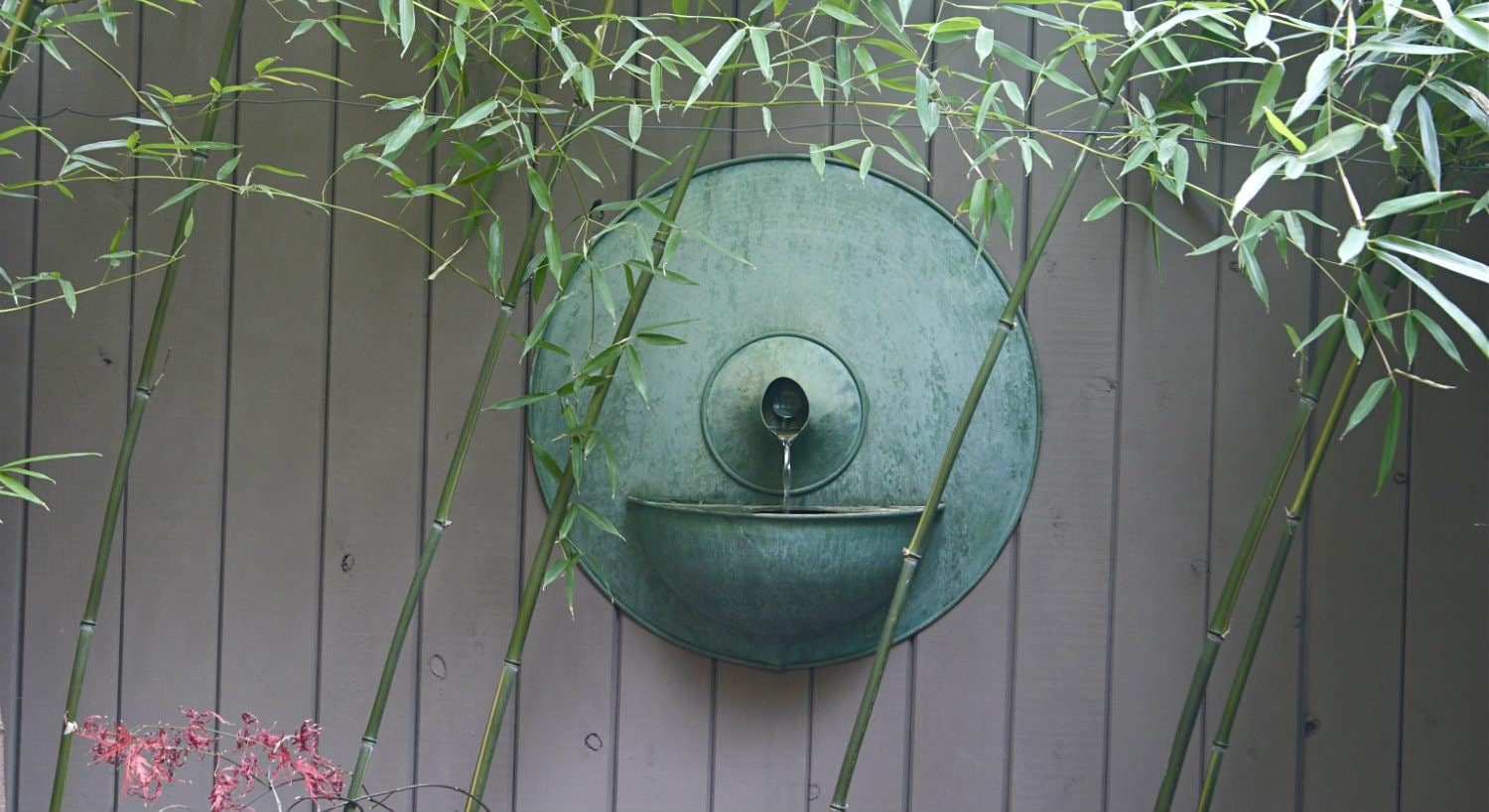 Outdoor antique wall fountain with green patina on wood wall