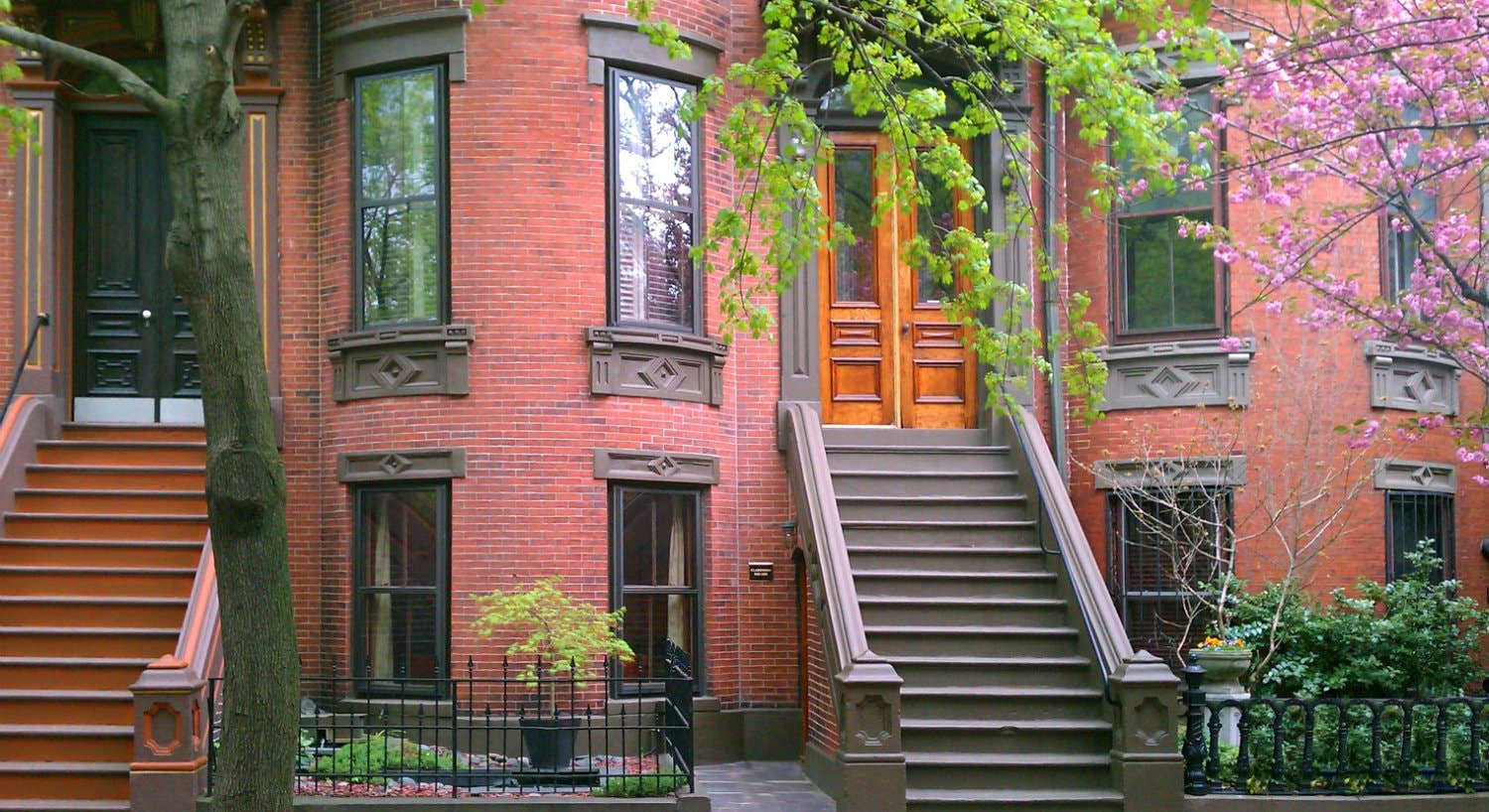 Red brick brownstone with wood trim and wood stained front door