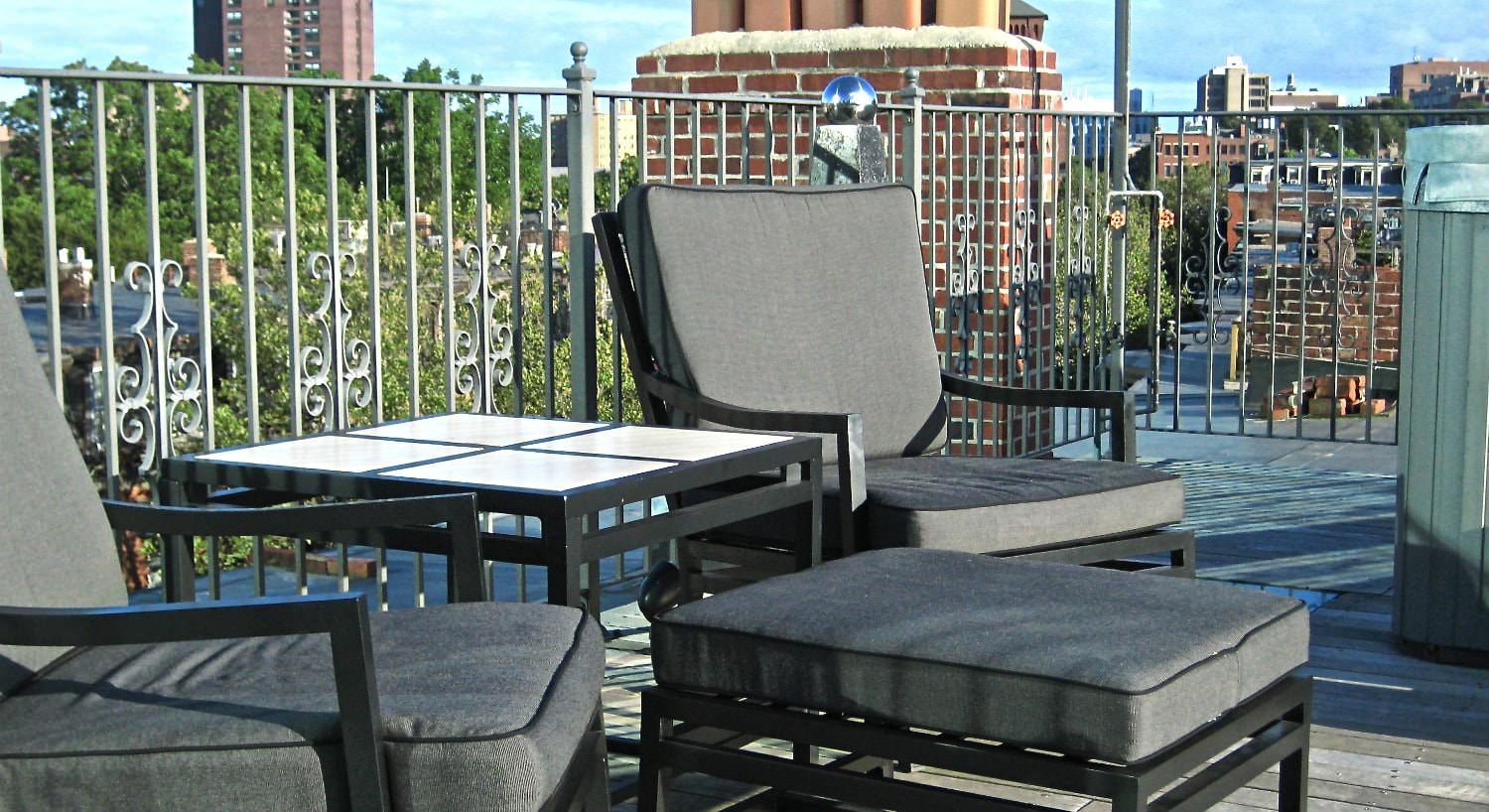 Rooftop terrace with gray and black furniture and gray scroll metal railing
