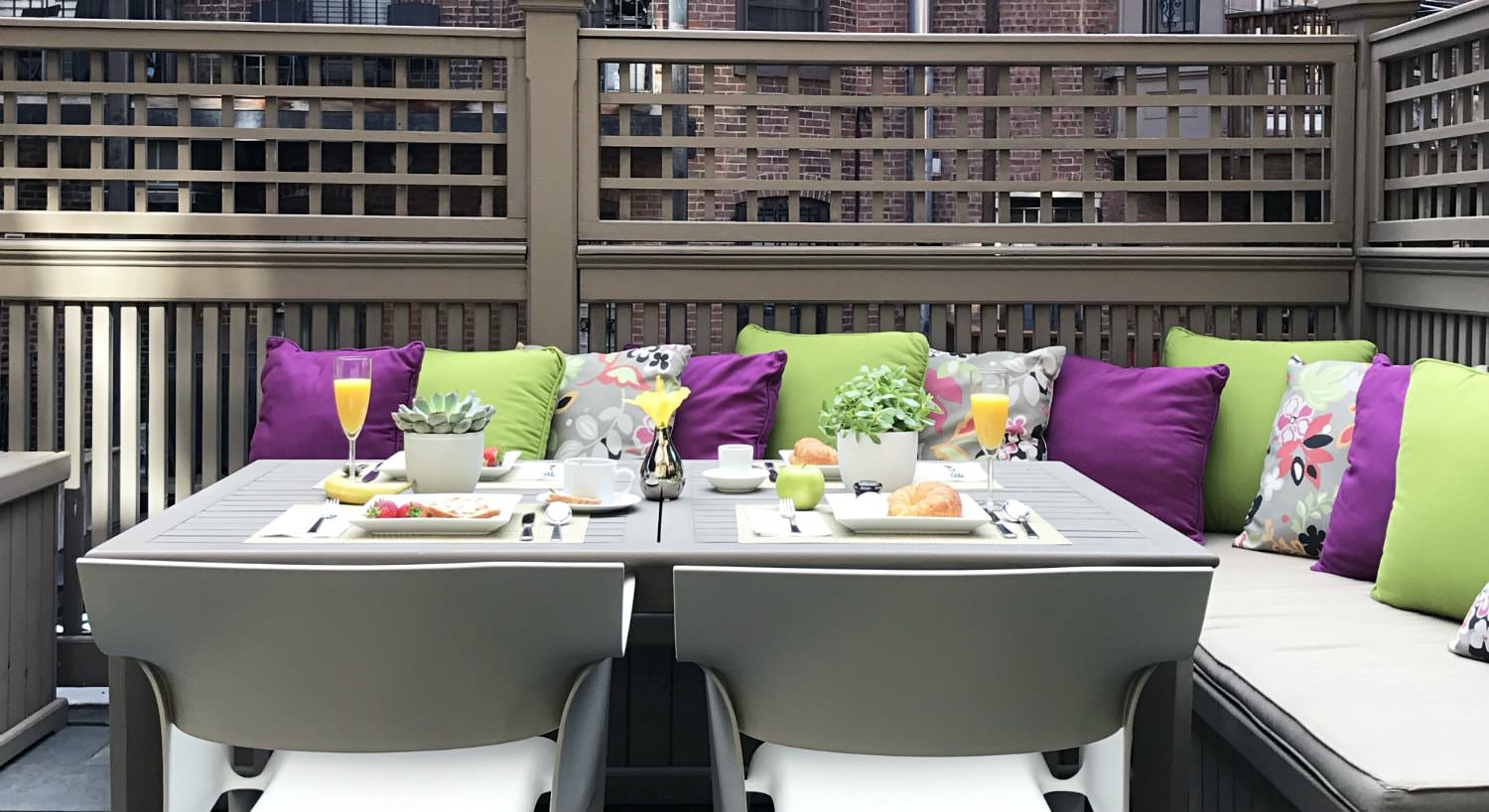Roof top deck with gray chairs, table, and bench seating topped with purple and lime green pillows