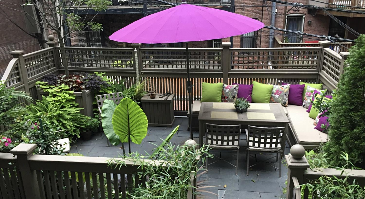 Terrace with slate floor, gray patio table and chairs, bench seating with green and purple pillows and pillow umbrella