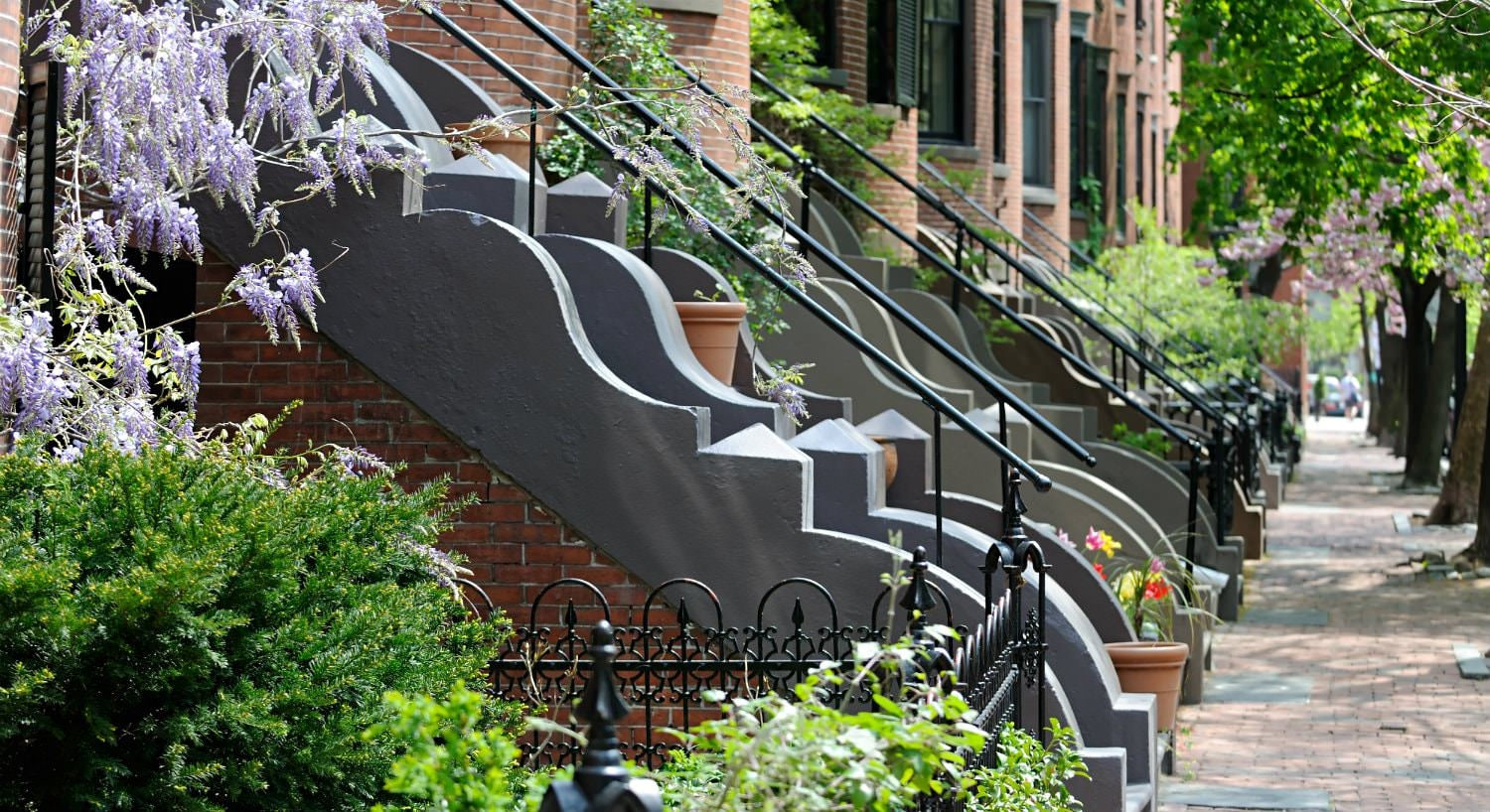 A row of decorative steps and railings leading up to brick brownstones