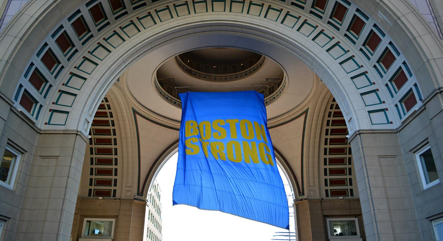 Blue and yellow Boston Strong flag hanging from an ornate stone atrium