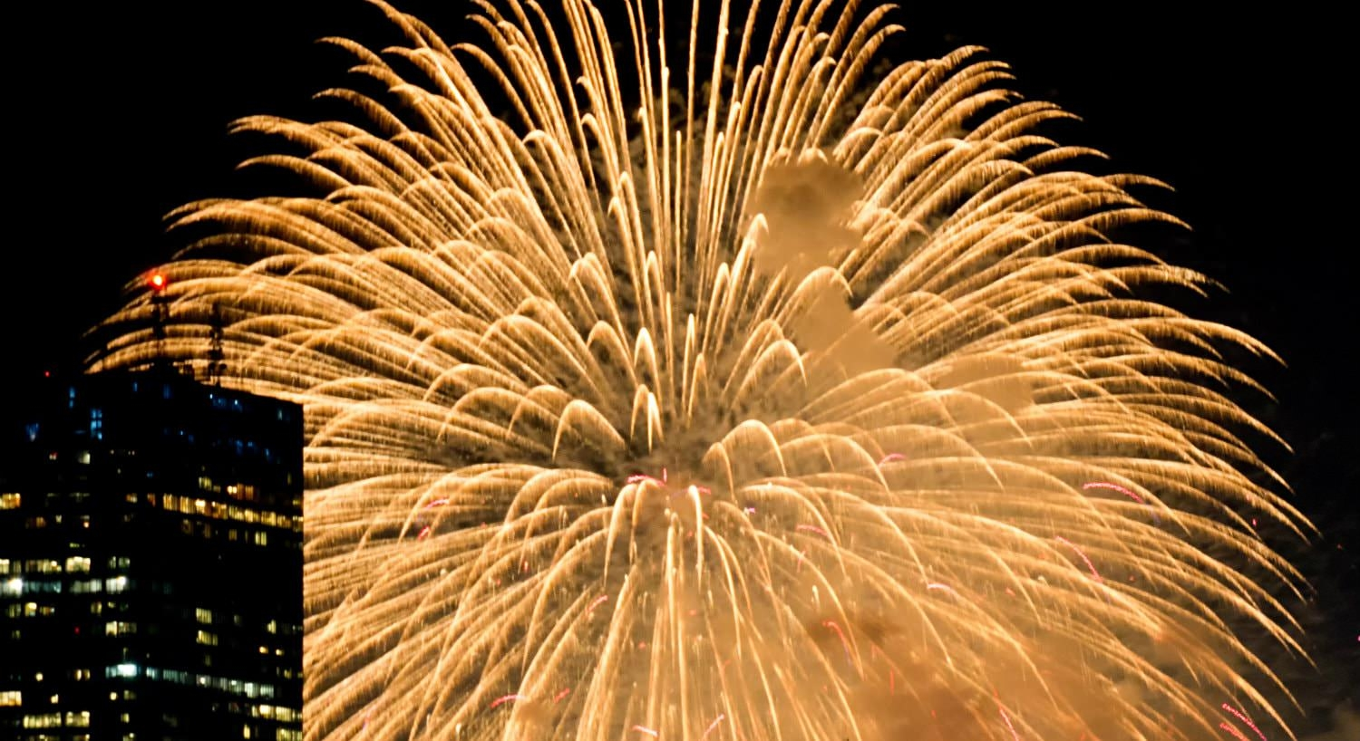 Large yellow burst of fireworks against a black sky