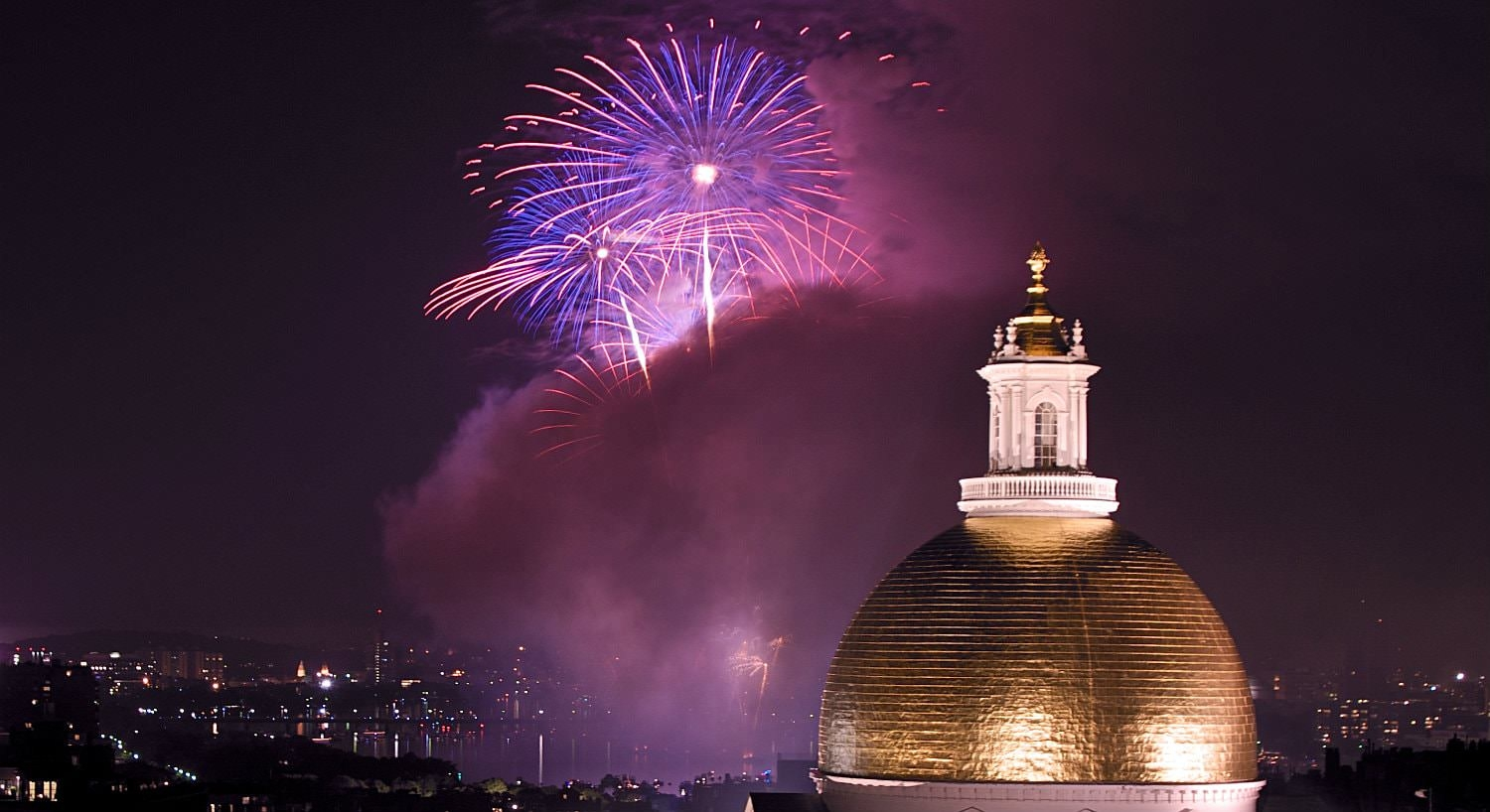 Purple and pink fireworks over the harbor and city lights with golden dome in the forefront
