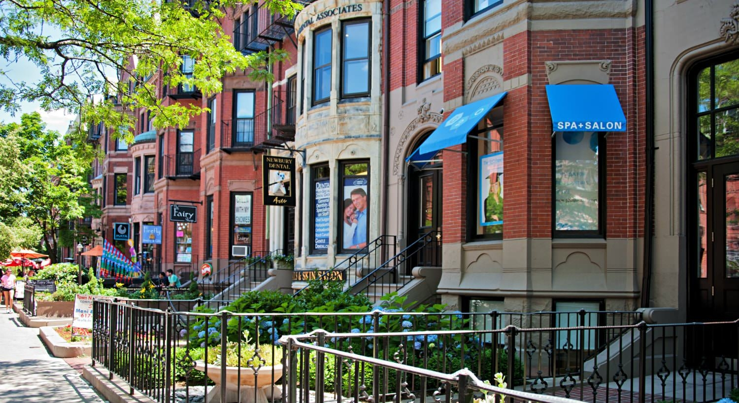 Row of red and beige brownstone storefronts with metal railings and green trees