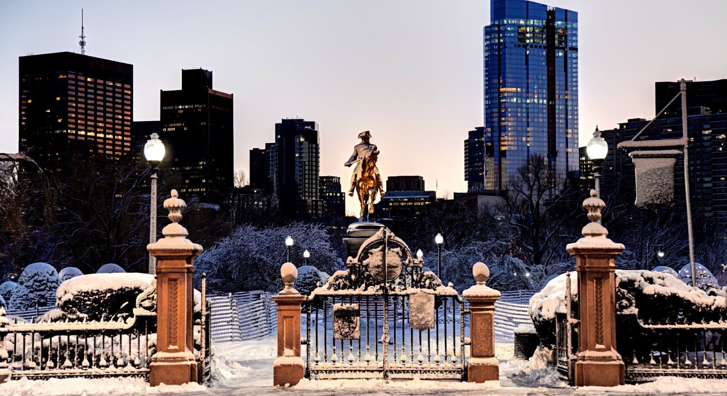 Bronze statue amidst a snow-covered park at dusk with lit up city buildings in the background