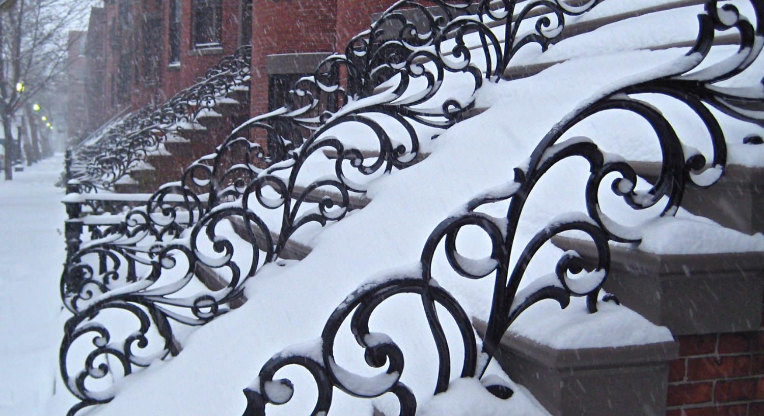 Row of red brick brownstones with scroll metal railings all covered in snow