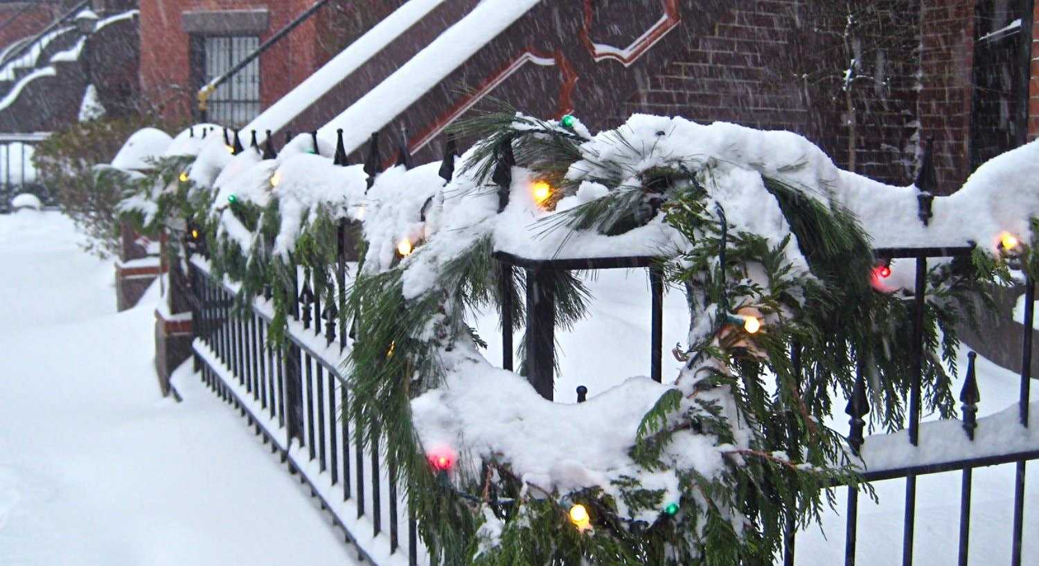 Row of red brick brownstones with black metal railings covered in greenery and white snow