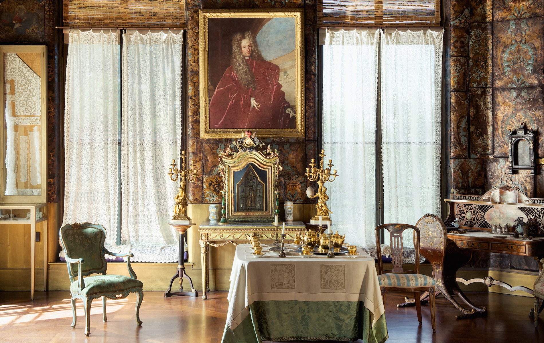 old fashioned room with table with white and green linen and a giant waiting of a man in a red cloak