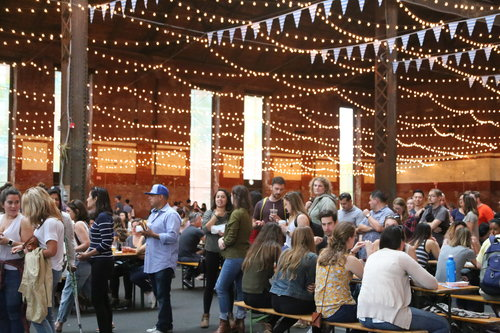 Crowd of people sitting at picnic tables in brick beer hall with several strands of small white lights