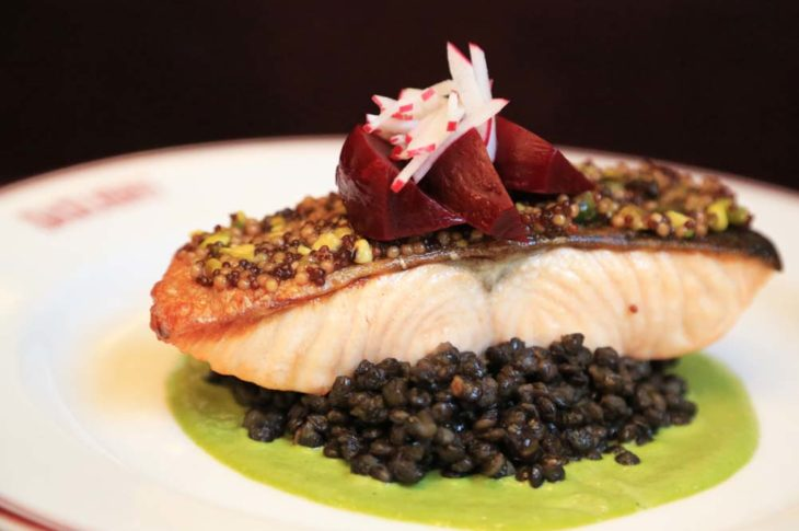 salmon on top of black lentils and a green sauce on a white plate