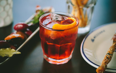 red cocktail with orange slice next to a white plate bread stick