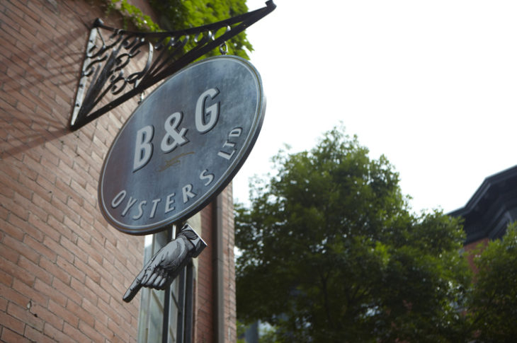black B&G sign with red brick and green tree