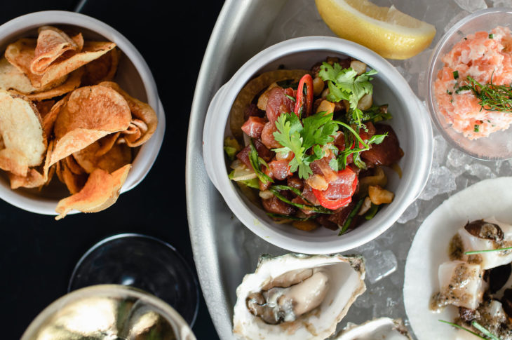 a bowl of orange sweet potato chips next to a tray of ice with 1 oyster 1 lemon wedge and 3 dishes of raw seafood