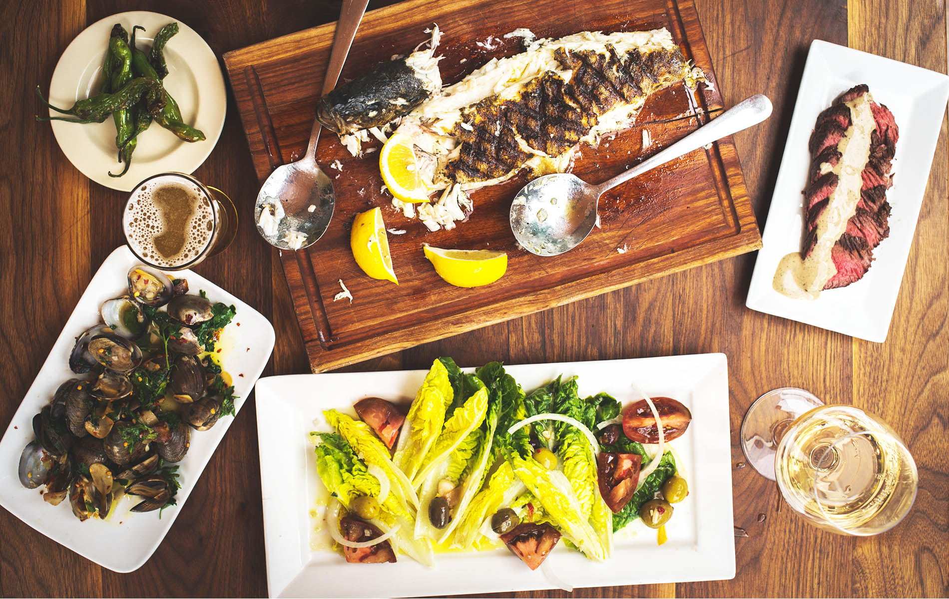 Wood table with food fish grilled lemons and yellow dish