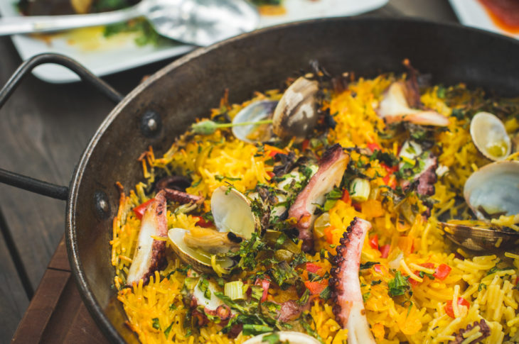 close up pan of yellow paella rice with silver spoon