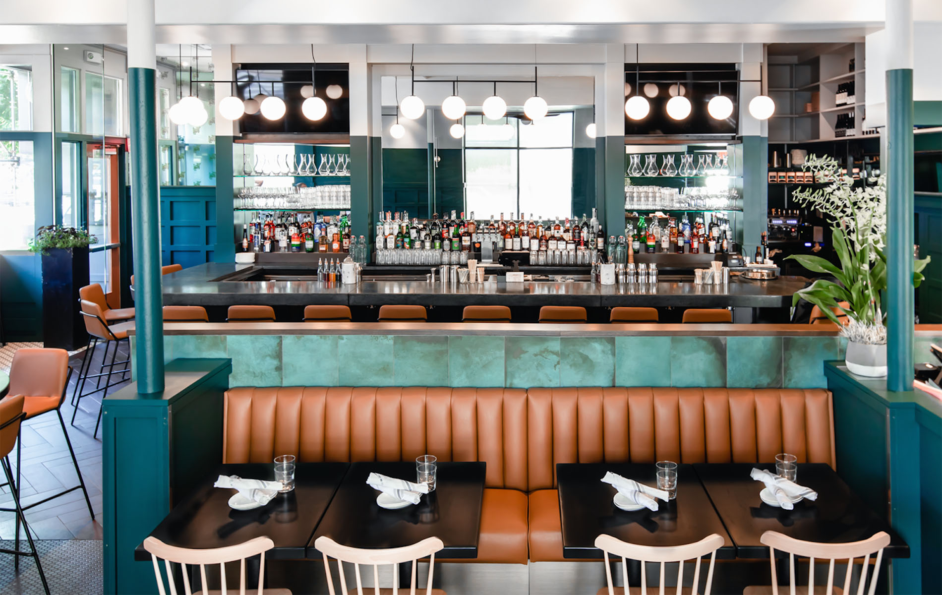 A restaurant with a brown leather booth and earth green walls with a bar behind and a dozen white hanging globe lights