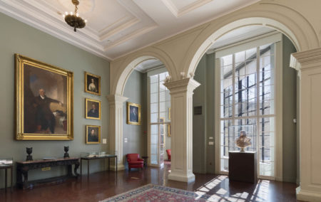historic room with hight green wall with 5 gold framed artworks and two white arches in front of the whindows
