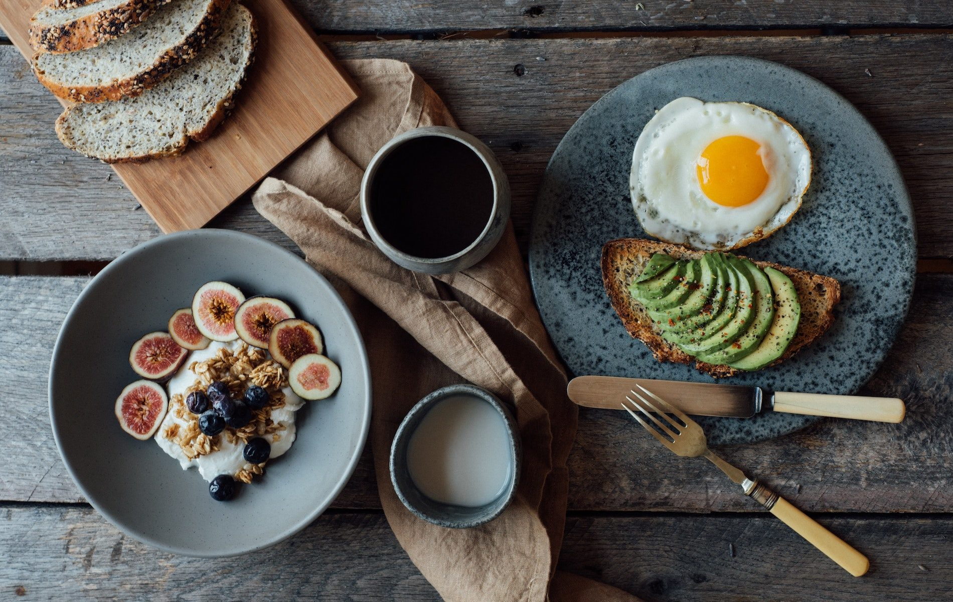 bowl of yogurt with sliced figs brown napkin black coffee cup of milk and avocado slicer with sunny side up egg