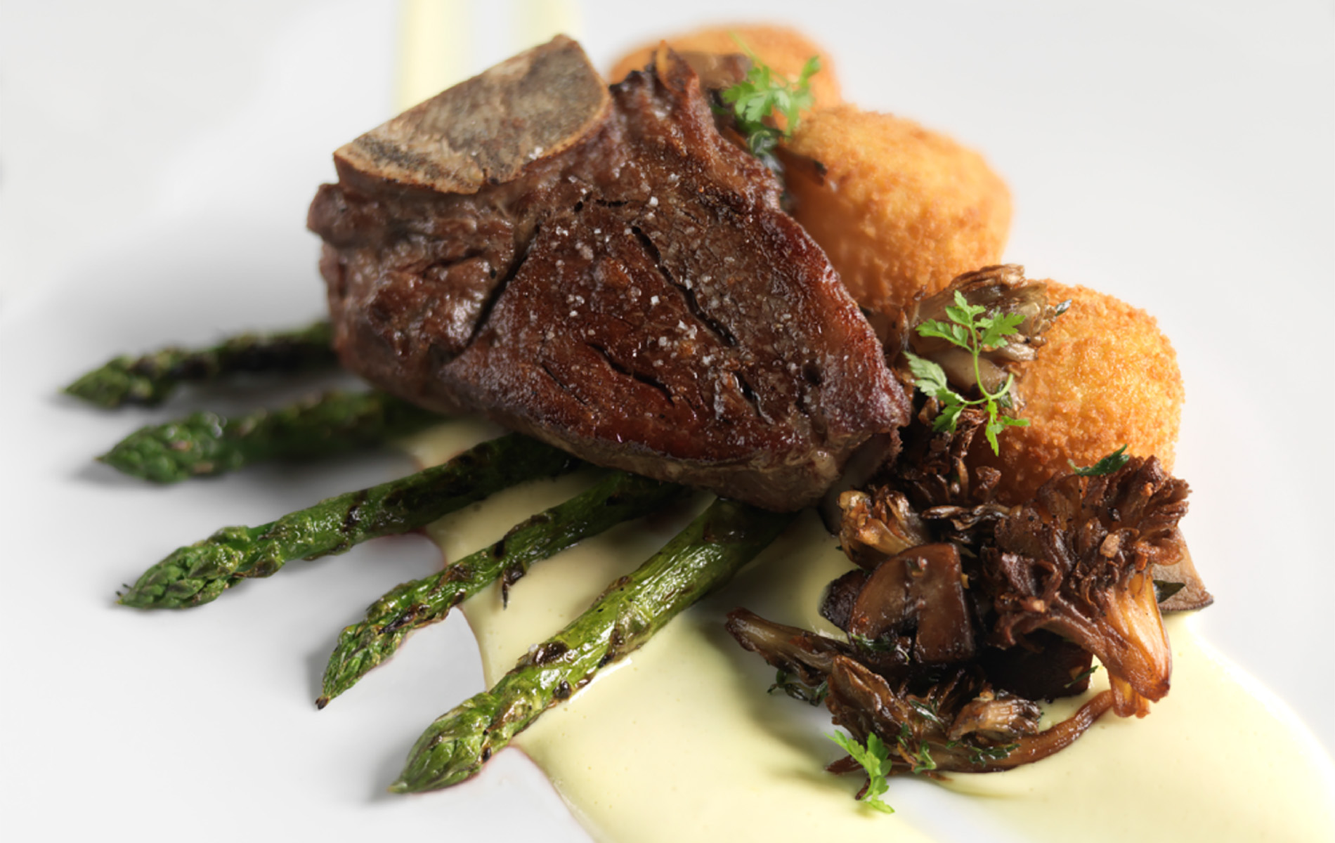 steak on top of green asparagus and a cream puree on a white plate