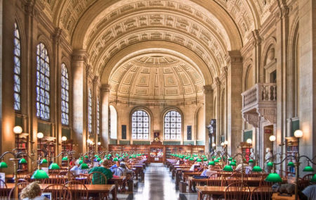 grand library with ornate white dome celling and two rows of wooden desk with green lamps
