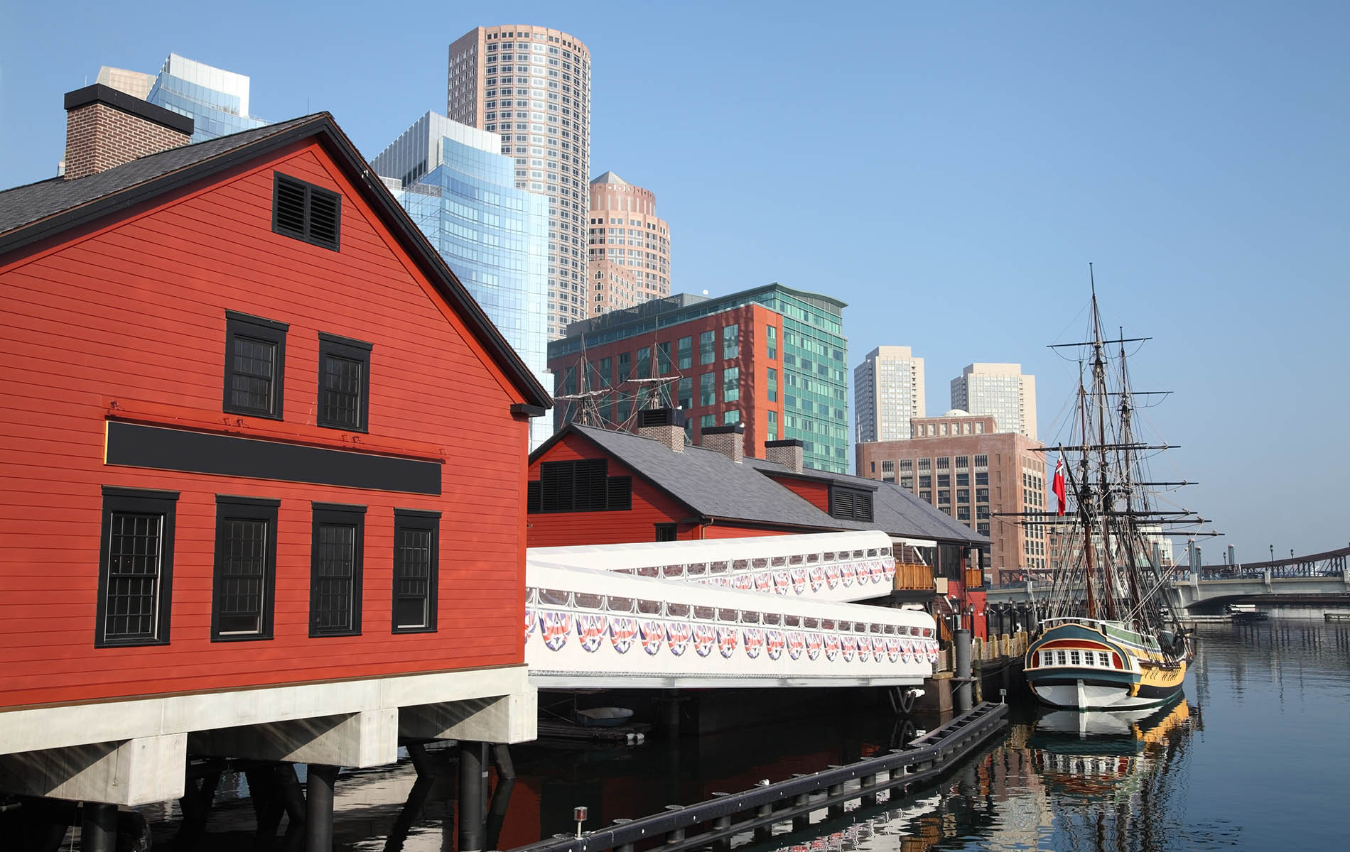 red building on a wharf with white railing walkway to boston tea party ship in water with clear blue sky
