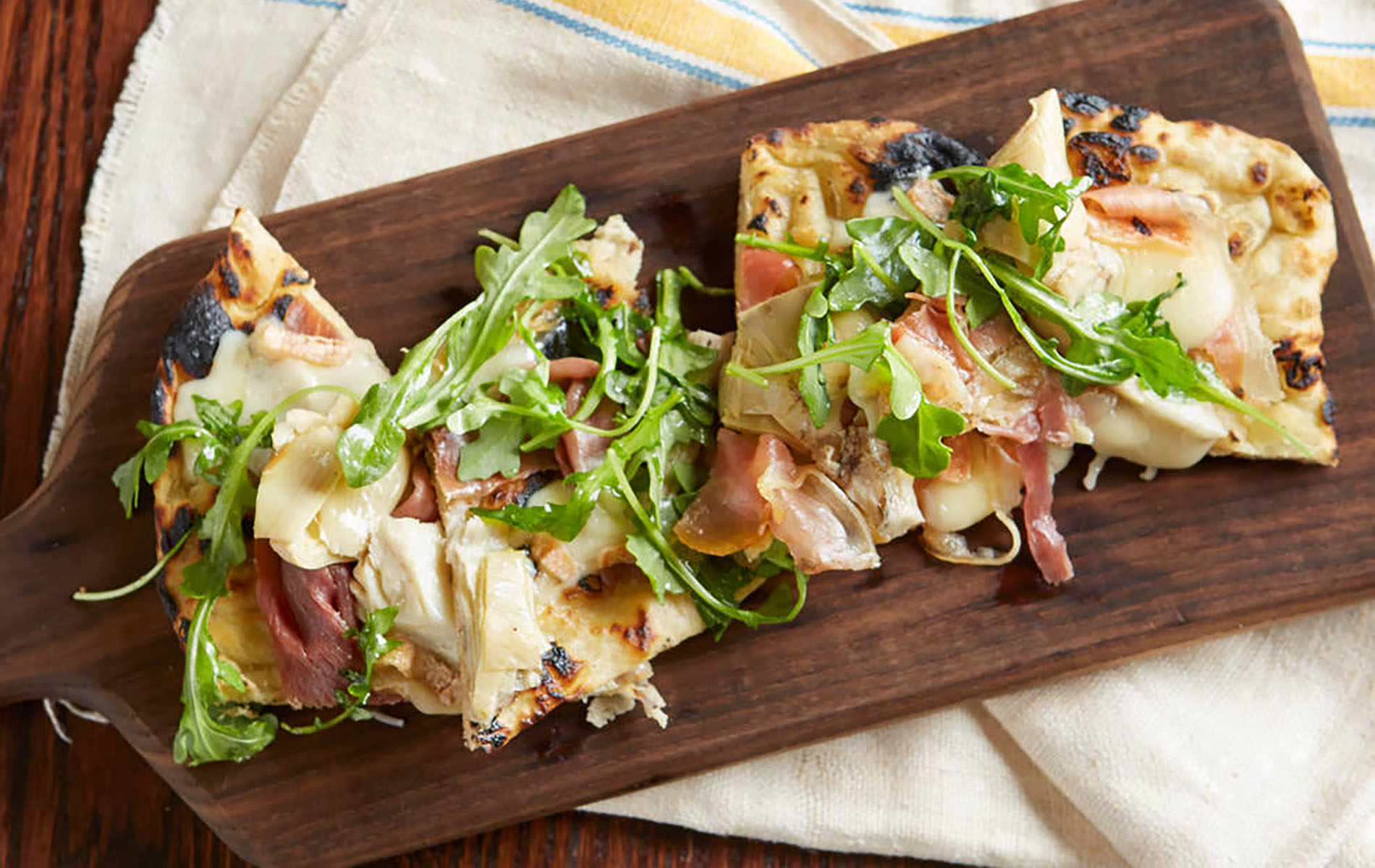 brown board with pizza of prosecution and arugula