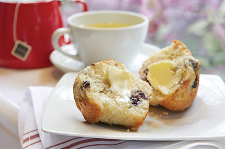 red teapot with white tea cup and saucer and muffin split in half with butter