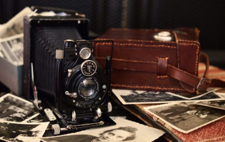 old fashioned camera on wood table with old photographs underneath