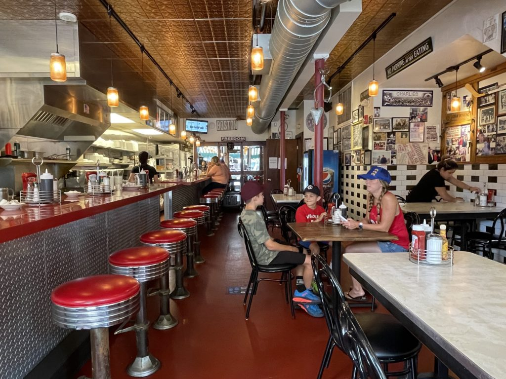 diner with 6 red stools on left and family on right 1 mom and two boys sitting at table