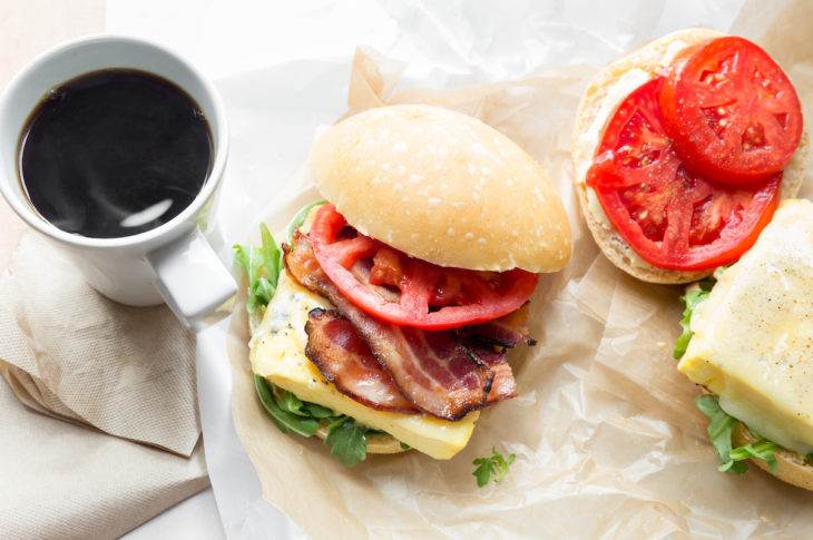 white mug with black coffee in middle a breakfast sandwich with white bun red tomato slice on top bacon and egg and red tomato on right