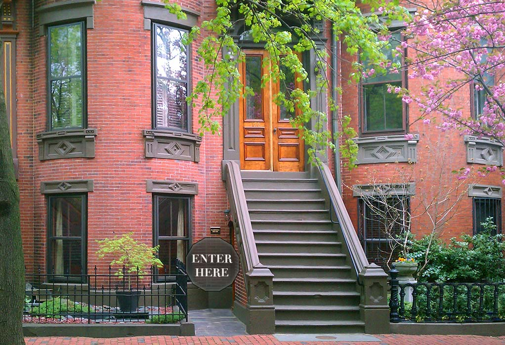 historic red brick building on tree lined street with external staircase