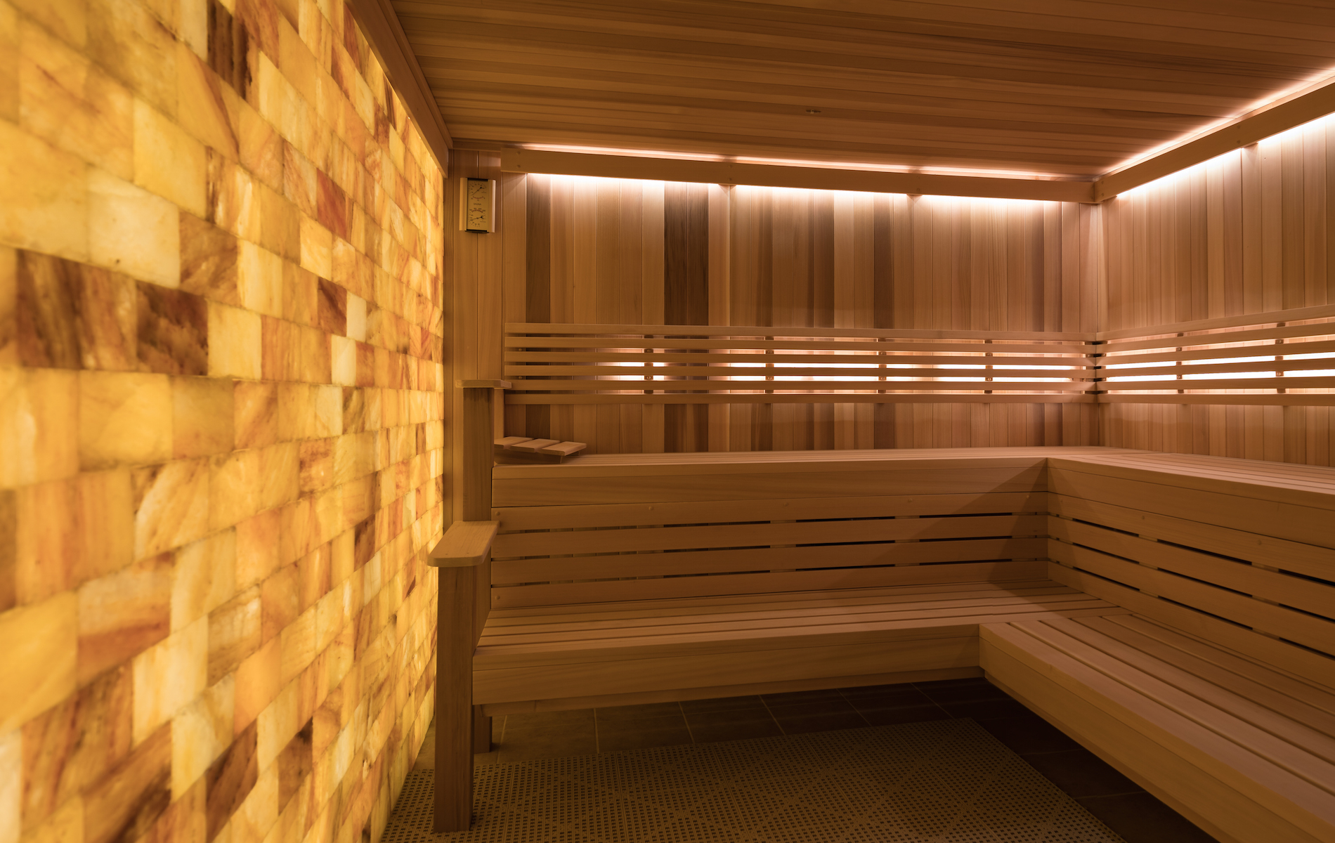 brown wood panel sauna with illuminated wall of salt bricks on left