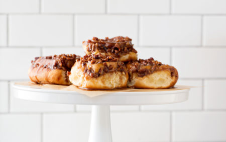 a stack of four pecan sticky buns on a white pedestal and a white tile background