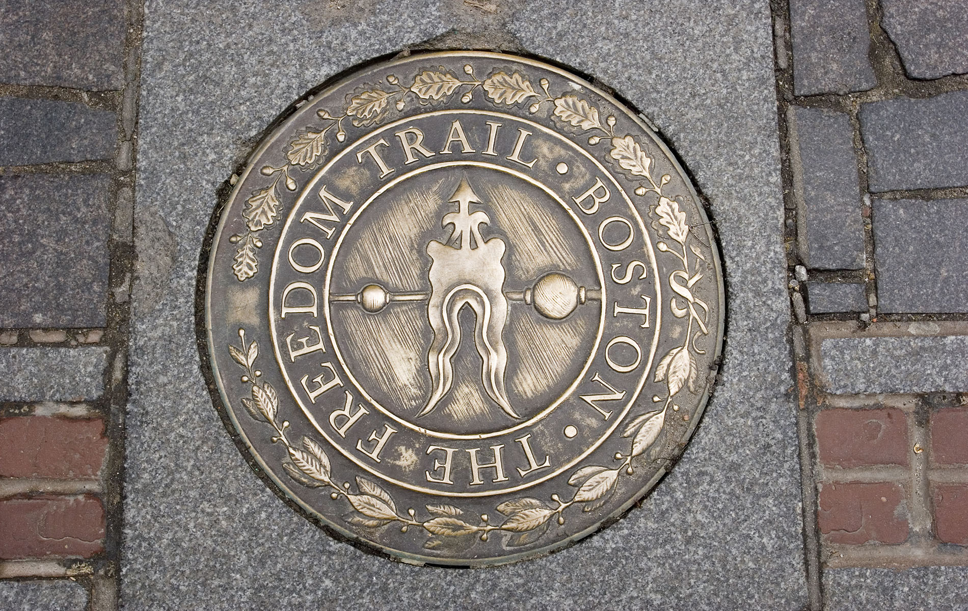 Freedom Trail bronze plaque on cement with red brick line