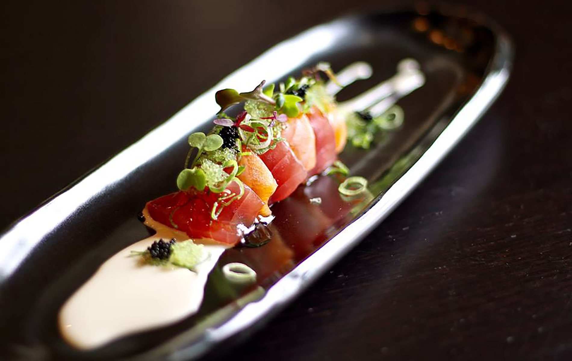 tuna sushi with scallions and white sauce on black plate