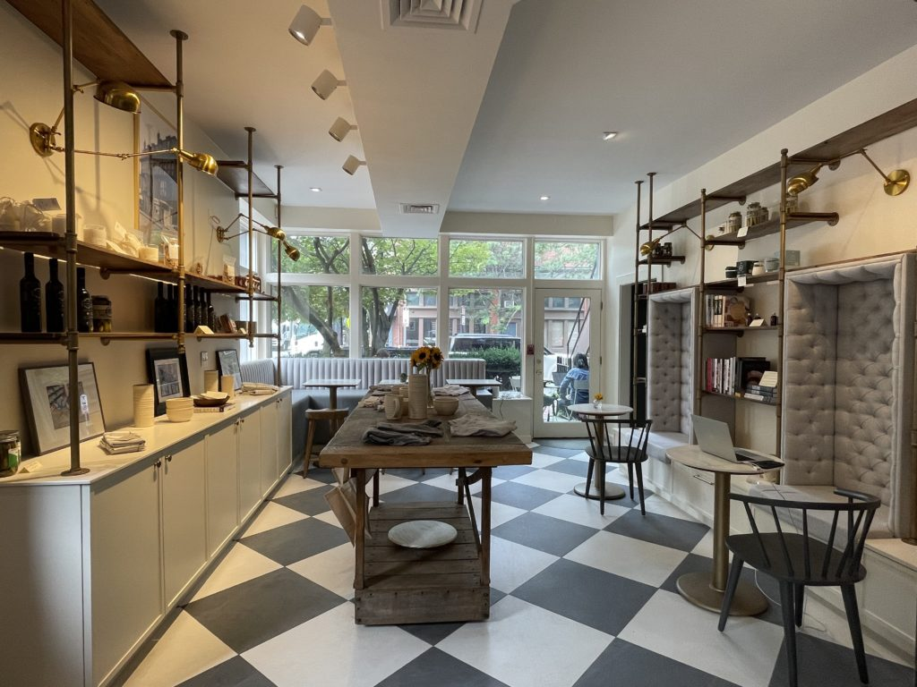 black and white checkered floor in cafe with one table and one booth along windows